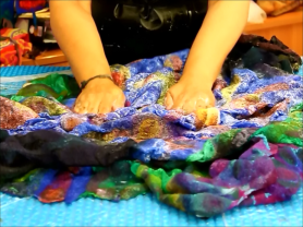 Joni Cornell of Wrapt in Felt nuno felting by rubbing her piece on a solar pool cover