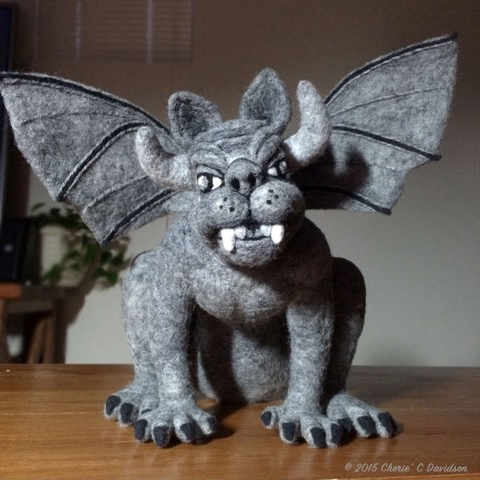 This fiber gargoyle is the size of a house cat, and has been sculpted by hand using a barbed needle and loose fibers through a method known as sculptural needle felting